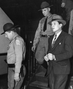 Convicted murderer Richard Dapper Dick Gallogly being escorted by two policemen following his return to Georgia, March 25 1940. Georgia State University Library