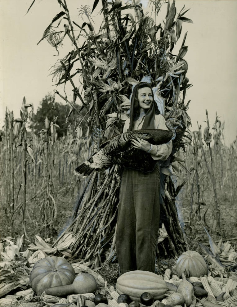 Taken at some point in the 1930's here is a woman in a cornfield with harvest vegetables holding a live turkey - Georgia State University Archives