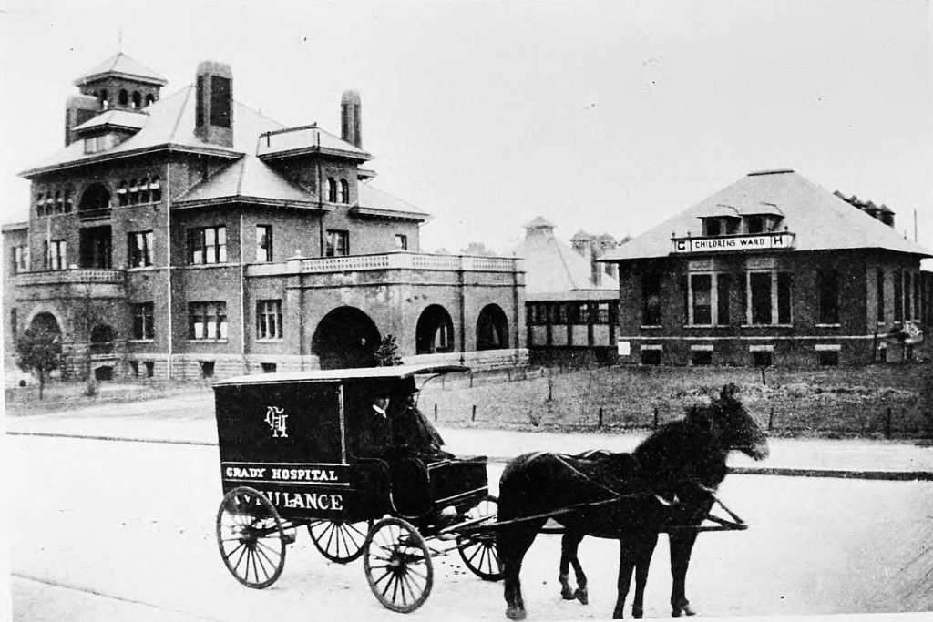 Horse-drawn Ambulance in 1896 Atlanta for Grady Hospital - Possibly the ambulance that rushed Baker Bass to Grady, which is in the background on the left - Georgia State University Libary
